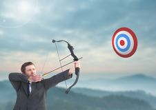 Businessman aiming at target with bow and arrow Royalty Free Stock Photos