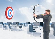 Businessman aiming at target with bow and arrow Royalty Free Stock Photography