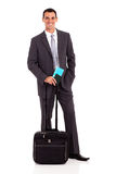 Businessman air ticket. Handsome young businessman with trolley bag and air ticket Royalty Free Stock Images