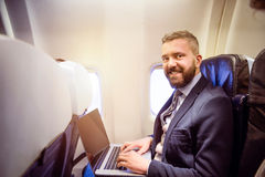 Businessman in airplane Royalty Free Stock Image