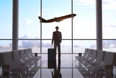 Businessman in airport. And airplane in sky stock photos