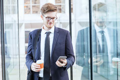 Businessman in the airport, checking email on smartphone Stock Image