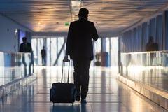 Businessman at airport corridor walking to departure gates. Stock Photo