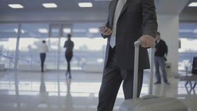 Businessman in the airport with his phone and suitcase. Close-up. Handsome businessman wearing the suit is in the airport hall. Attractive man holds his phone in stock video