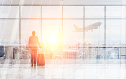 Businessman in airport. Businessman with luggage facing windows in airport with New York city view and an airplane flying by Royalty Free Stock Photography