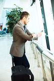 Businessman at airport with smartphone and suitcase Royalty Free Stock Image