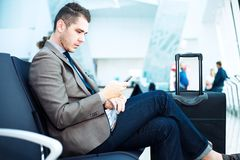 Businessman at airport with smartphone and suitcase Stock Images