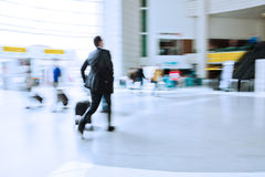Businessman at the airport. Traveling businessman with a trolley at the airport Stock Photos