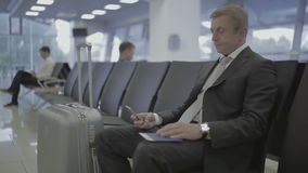 Businessman in the airport waiting hall. Handsome businessman waits for boarding at the airport waiting hall. Businessman looks at his phone. Attractive man stock video