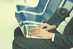 Businessman in airport waiting lounge typing on laptop Royalty Free Stock Images