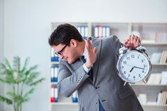 The businessman with alarm clock in the office Royalty Free Stock Photography