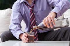 Businessman and alcoholism. An elegant man suffering from alcoholism drinking whisky royalty free stock images