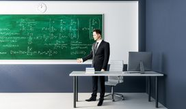 Businessman with algebra formulas. Businessman standing in modern classroom interior with algebra formulas on chalkboard. Science, education and lesson concept royalty free stock photos