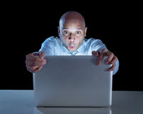 Businessman alone at night sitting at computer laptop watching or online gambling Stock Photo