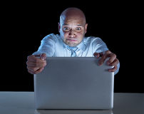Businessman alone at night sitting at computer laptop watching porn or online gambling Stock Images