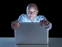 Businessman alone at night sitting at computer laptop watching porn or online gambling Stock Photo