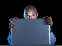 Businessman alone at night sitting at computer laptop watching porn or online gambling Royalty Free Stock Photo