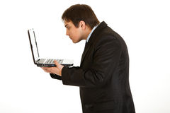 Businessman amazedly looking in laptops screen. Young businessman amazedly looking in laptops screen isolated on white Royalty Free Stock Image