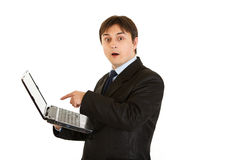 Businessman amazedly looks in laptops screen. Modern businessman amazedly looks in laptops screen isolated on white Royalty Free Stock Images