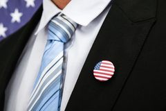 Businessman with american badge. Close-up Of Businessman In Suit Wearing American Badge Royalty Free Stock Image