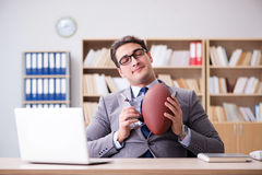 The businessman with american football in office Royalty Free Stock Photo