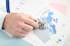 Businessman analysing an economic document with a stethoscope Royalty Free Stock Images