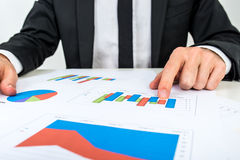 Businessman analysing a set of bar graphs. As he sits at his desk pointing to one column chart, in a business analysis, projections and strategy concept Stock Photography