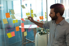 Businessman analyzing adhesive notes on glass Stock Photos
