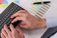 Businessman analyzing data. Close up of man hands typing on computer keyboard Stock Image