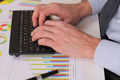 Businessman analyzing data. Close up of man hands typing on computer keyboard Royalty Free Stock Image