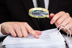 Businessman analyzing document. Businessman Looking At Document Through Magnifying Glass stock photo