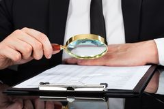 Businessman analyzing document with magnifying glass at desk Stock Photo