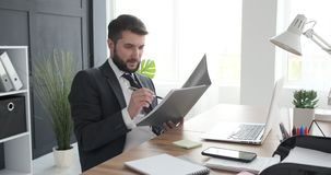 Businessman reading documents and working on laptop stock video