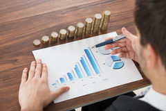 Businessman Analyzing Financial Graph. Close-up Of Businessman Analyzing Financial Graph In Front Of Stacked Coins Stock Image