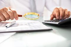 Businessman Analyzing Financial Report With Magnifying Glass stock photos