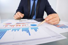 Businessman analyzing graph papers stock photography