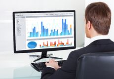 Businessman analyzing graphs on computer at desk. Rear view of young businessman analyzing graphs on computer at desk in office Royalty Free Stock Photos