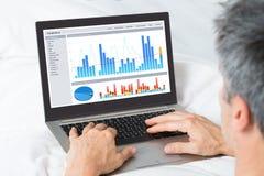 Businessman Analyzing Graphs On His Laptop Stock Photo