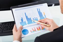 Businessman analyzing graphs at office desk Stock Photos