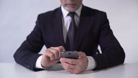 Businessman analyzing growth of production costs at enterprise, using smartphone. Stock footage stock footage