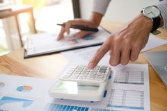 Businessman analyzing investment charts and pressing calculator Royalty Free Stock Images