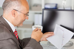 Businessman Analyzing Line Graph While Holding Coffee Cup Royalty Free Stock Photography