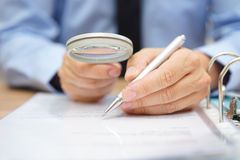 Businessman is analyzing  through  magnifying glass   Stock Photos