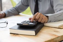 Businessman analyzing report on chart with calculator Stock Photo