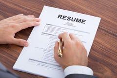 Businessman analyzing resume at desk Stock Photo