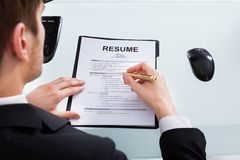Businessman analyzing resume at office desk royalty free stock images