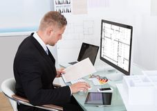 Businessman analyzing a spreadsheet online checking Stock Photos