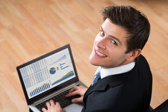 Businessman Analyzing Statistical Data On Laptop. Young Happy Businessman Analyzing Statistical Data On Laptop In Office Stock Images