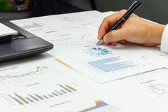 Businessman analyzing Summary report and financial plan. Product, pen and calculator on paperwork Stock Photo
