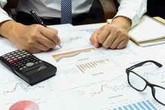 Businessman analyzing Summary report and financial . Businessman analyzing Summary report and financial total market plan, pen and calculator on paperwork Royalty Free Stock Photos